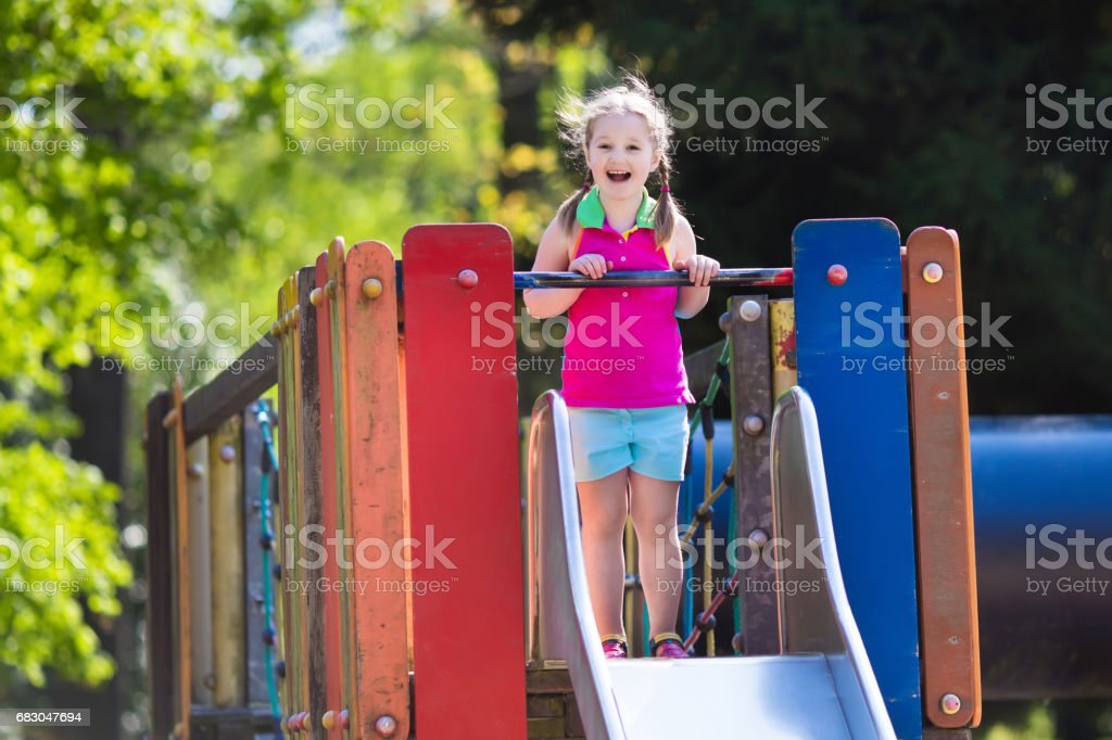 Child playing on outdoor playground in summer foto de stock royalty-free