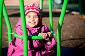 Toddler aged 3 years old is sitting on the merry-go-around in playground. She wears a winter coat and bonnet as it's a cold winter day. This file has a