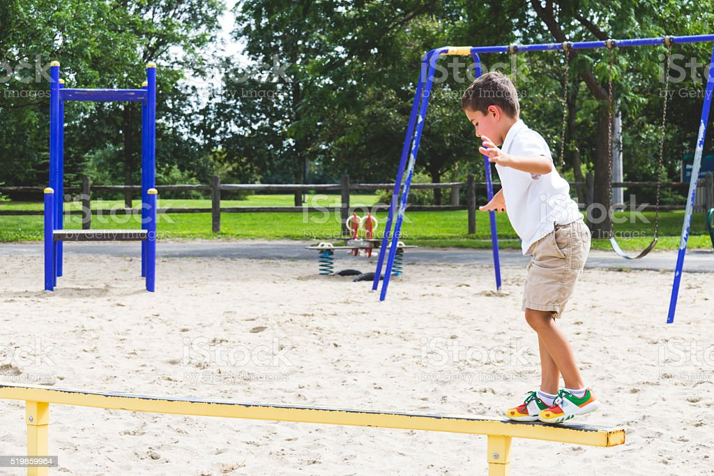 Child playing on the park play structure balance beam stock photo