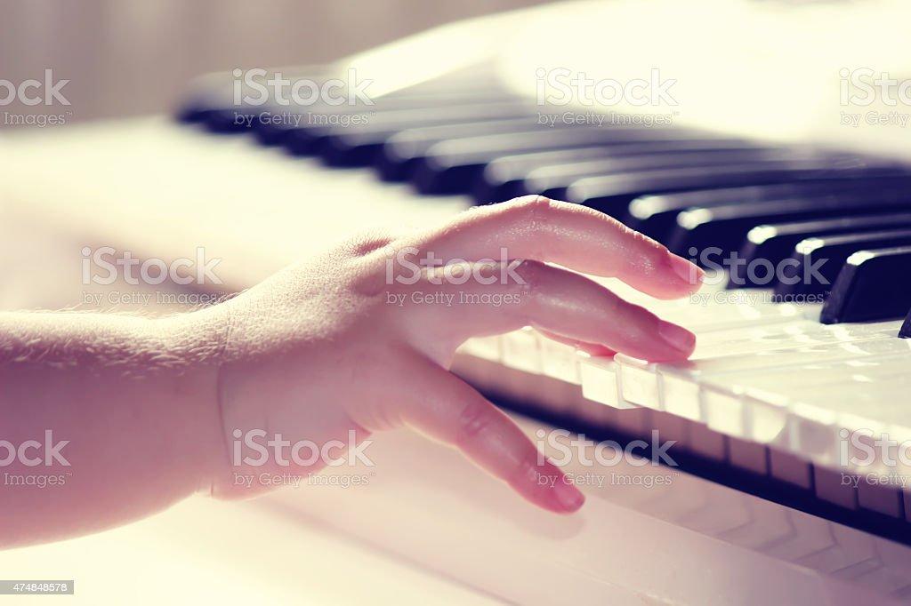Child playing piano stock photo