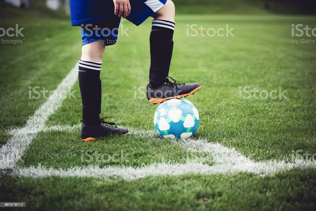 Child playing soccer at local stadium outside on grass field. Lower...