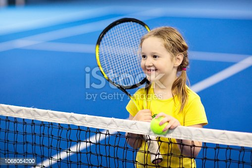 1153628111istockphoto Child playing tennis on indoor court 1068054200