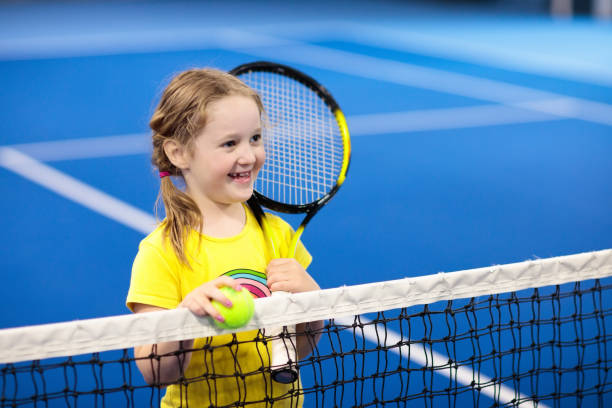 child playing tennis on indoor court - racket sport stock pictures, royalty-free photos & images