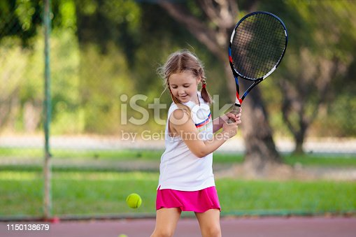 Child playing tennis on indoor court. Little girl with tennis racket and ball in sport club. Active exercise for kids. Summer activities for children. Training for young kid. Child learning to play.