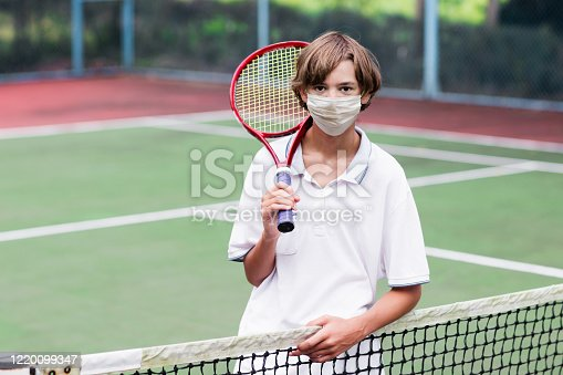 Boy in face mask playing tennis on outdoor court during coronavirus outbreak. Teenager with tennis racket and ball in sport club. Active exercise for kids. Social distancing. Training in pandemic.