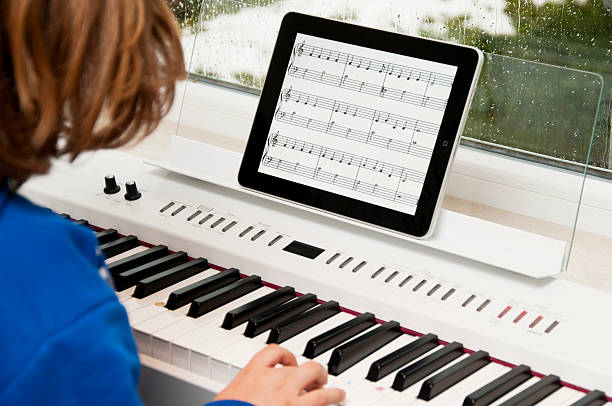 child playing the piano with iPad as sheet of music stock photo