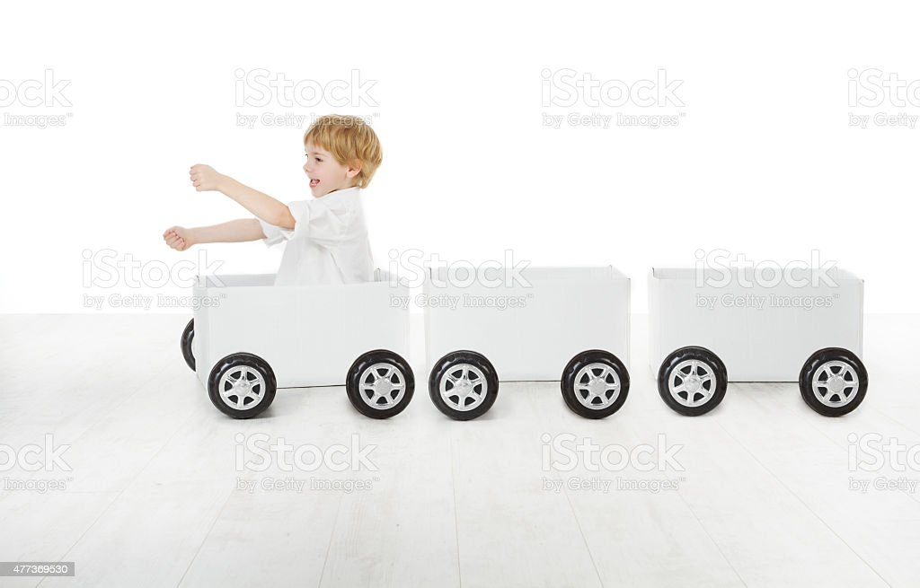 Child Playing Toy Car, Kid Driving Train Wagons Empty Boxes stock photo