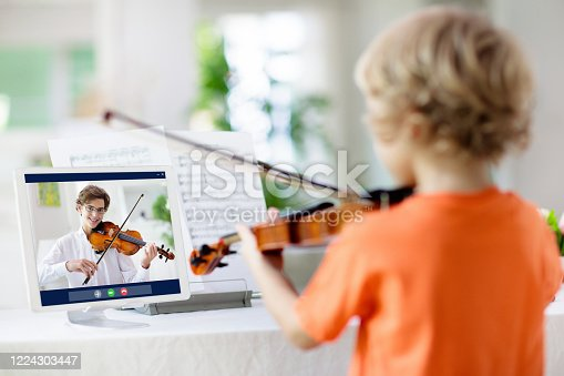 istock Child playing violin. Remote learning. 1224303447