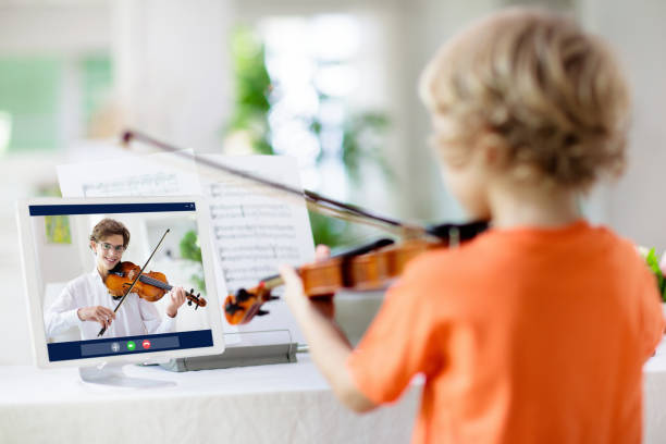Child playing violin. Remote learning. stock photo