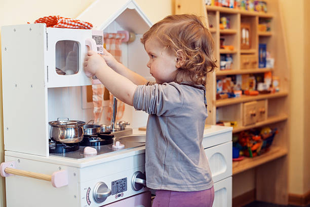 A child playing with a fake kitchen toddler girl playing toy kitchen kids cleaning up toys stock pictures, royalty-free photos & images