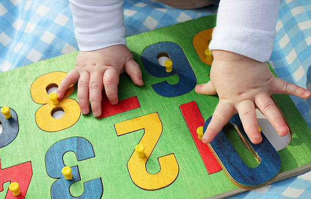 child playing with a number puzzle - preschool building stock photos and pictures