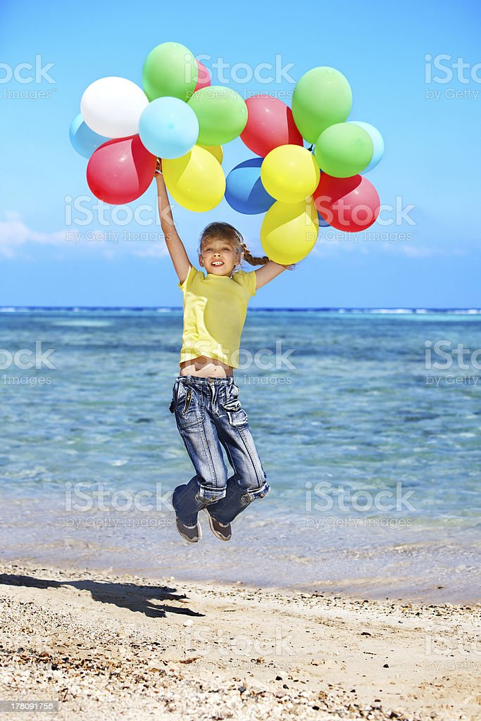 Child playing with balloons at the beach royalty-free stock photo
