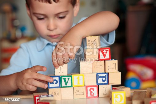 istock Child playing with blocks 166073307