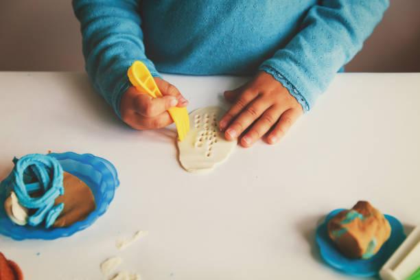kind spielt mit lehm zierleisten formen - knete spiele stock-fotos und bilder