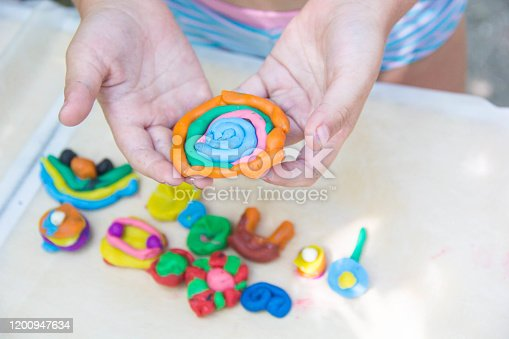 Child playing with colorful clay making animal figures. closeup on hands.