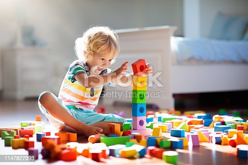istock Child playing with colorful toy blocks. Kids play. 1147827393