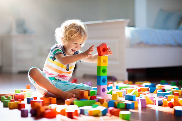 Child playing with colorful toy blocks. Kids play. stock photo