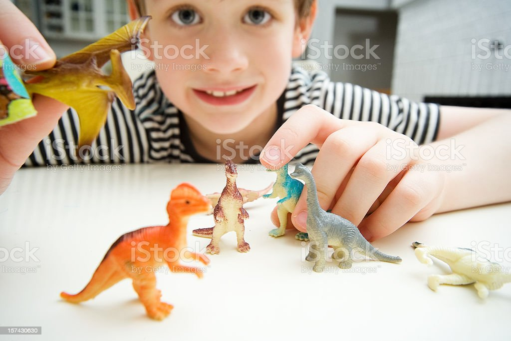 Child Playing with Dinosaurs in Kitchen Lifestyle stock photo