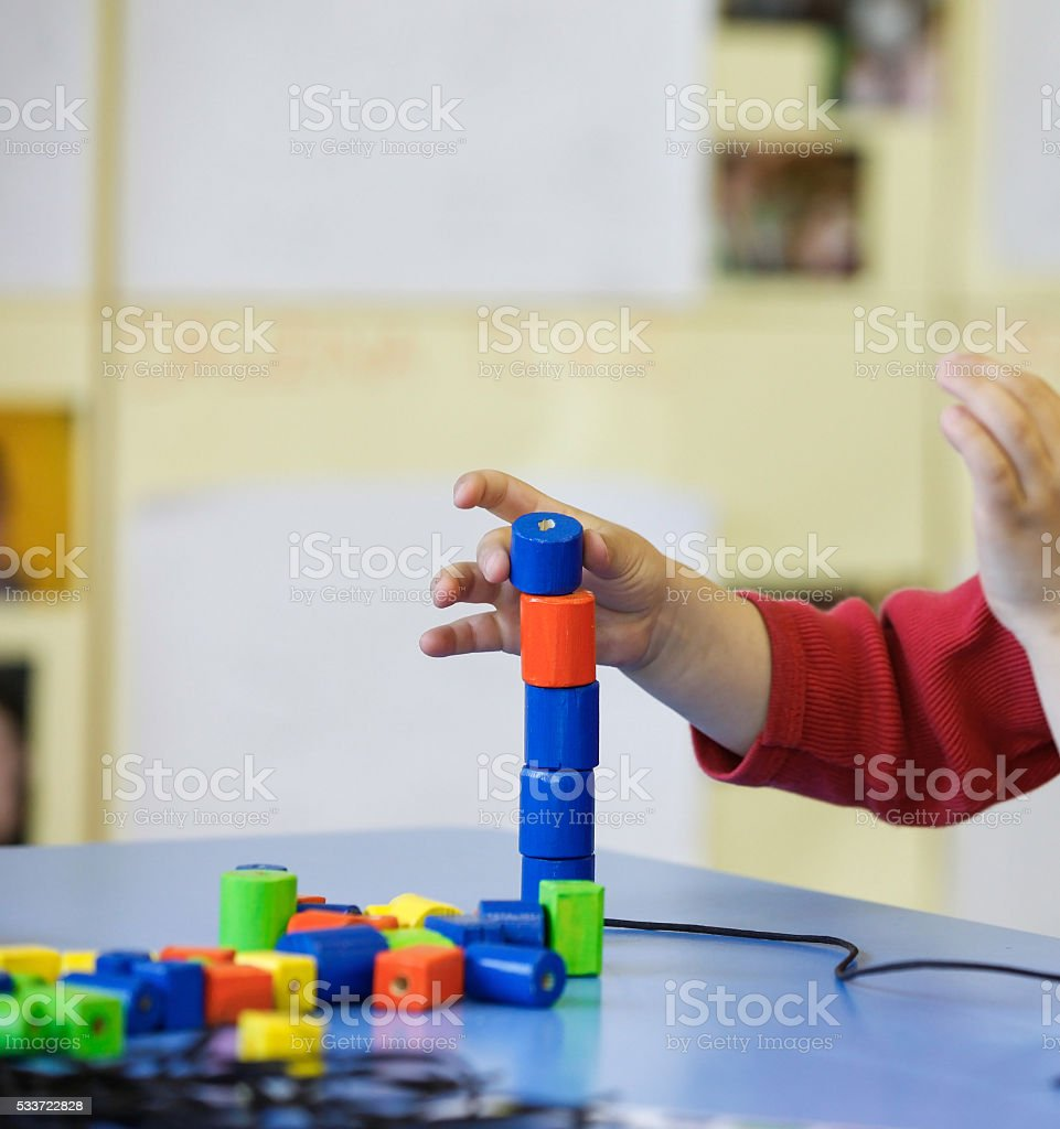 Child playing with do-it-yourself educational toys stock photo