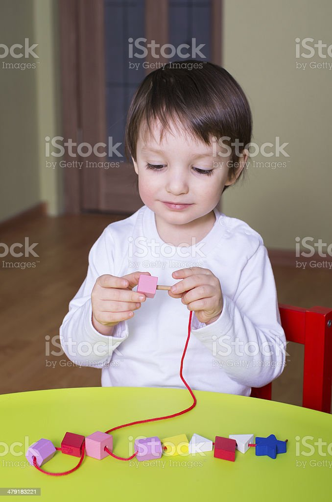 child playing with educational toys Lacing royalty-free stock photo
