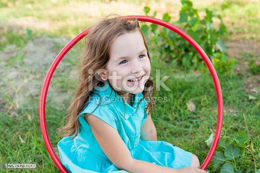 Child playing with hula hoop and training her skills in summer. Cheerful Exercise Concept . happy girl having fun with hula hoops outdoor. activity for the baby concept