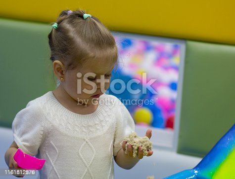 child playing with kinetic sand at home