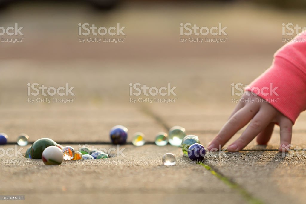 Kind spielt mit Marmor auf dem Bürgersteig stehen. – Foto