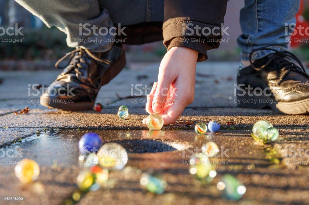 Kind spielt mit Murmeln auf Yhe Bürgersteig. altmodische Spielsachen noch gebräuchlich heute. – Foto
