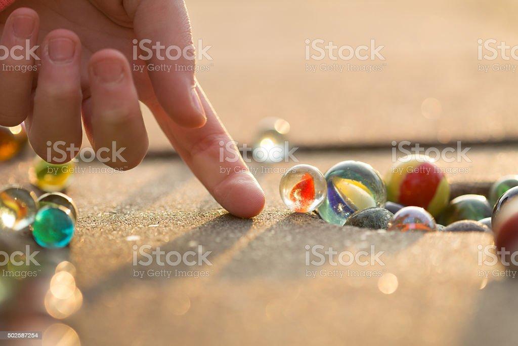 Kind spielt mit Marmor auf yhe Gehweg. – Foto