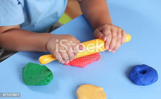 Children's hands with rolling-pin playing modeling clay.