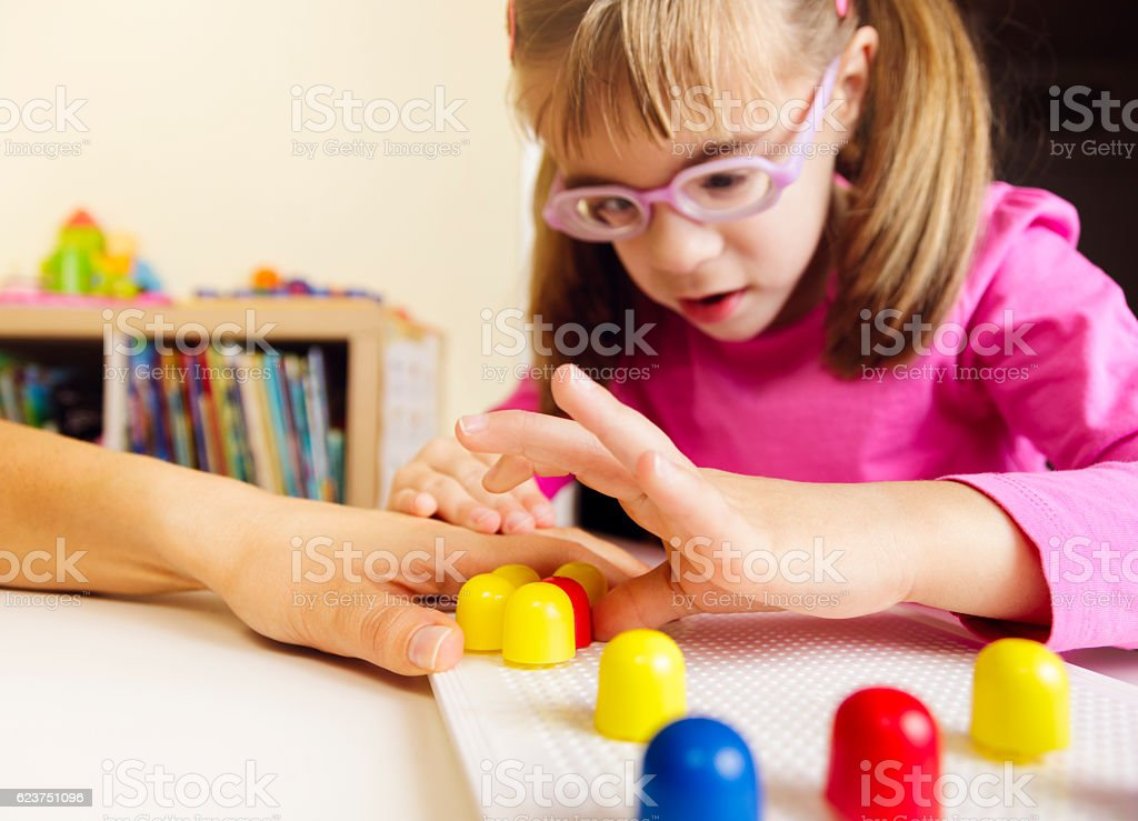 Child playing with mosaic peg board with teacher stock photo