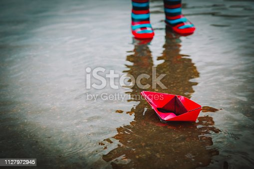 istock child playing with paper boats in water puddle 1127972945