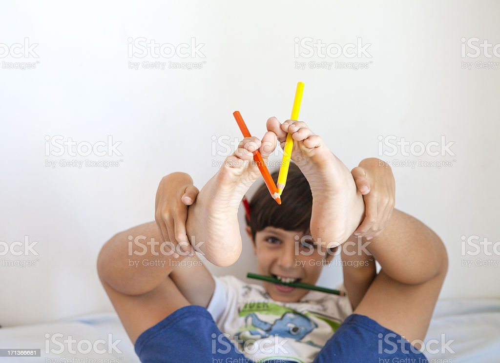 Child Playing with Pensil on his Foot stock photo