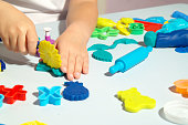 istock Child playing with playdough on the pastel blue table. A lot of toys on the table. Forms, dough roller and scissors. Happy child has fun with toys. 1285827637