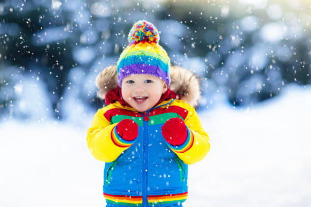 child playing with snow in winter. kids outdoors. - mitene imagens e fotografias de stock