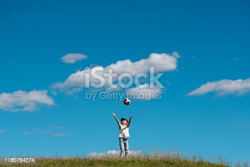 Child playing with soccer ball in meadow