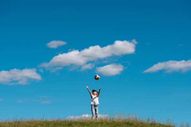 enfant jouant avec le ballon de football dans le pré - nuage 6 photos et images de collection