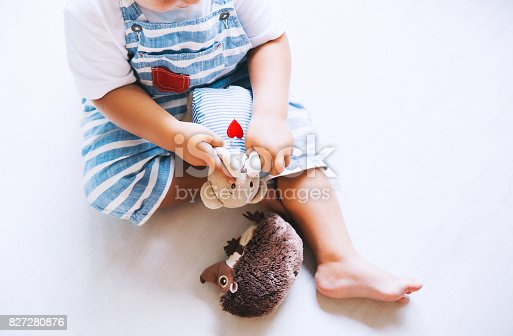 istock Child playing with soft toys at home on the floor. 827280876