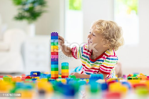 648139780 istock photo Child playing with toy blocks. Toys for kids. 1137822098