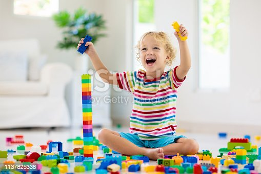 648139780 istock photo Child playing with toy blocks. Toys for kids. 1137825338