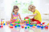 Kids play with colorful blocks. Little boy and girl build tower at home or day care. Educational toy for young child. Construction creative game for baby or toddler kid. Mess in kindergarten playroom.