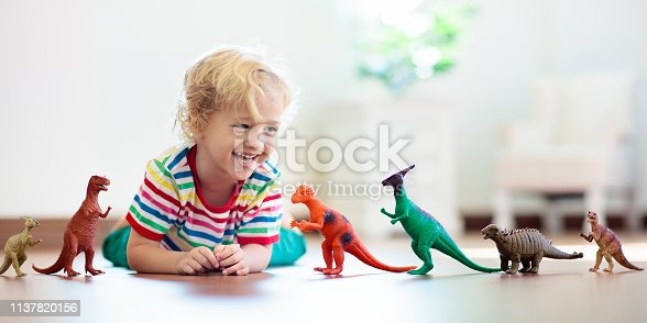 istock Child playing with toy dinosaurs. Kids toys. 1137820156