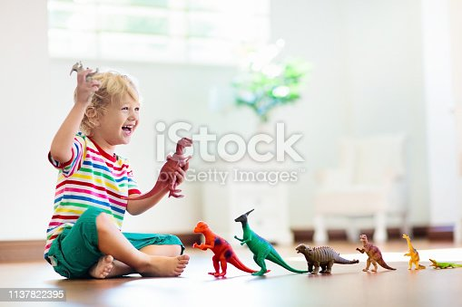 istock Child playing with toy dinosaurs. Kids toys. 1137822395