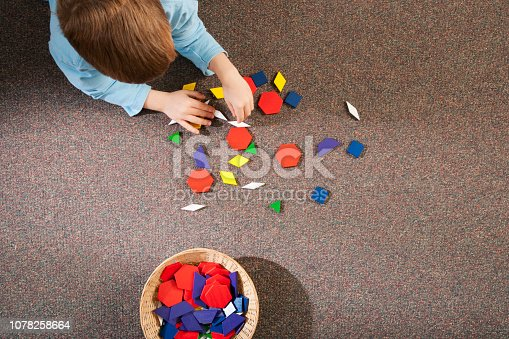 Child playing with toy shapes on carpet in grade school classroom