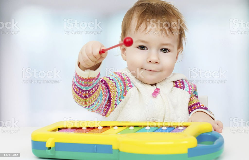 Child playing with toy xylophone stock photo