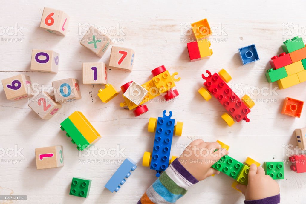Child playing with wooden cubes with numbers and colorful toy bricks on a white wooden background. Toddler learning numbers. Hand of a child taking toys. stock photo