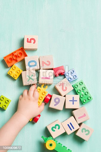 istock Child playing with wooden cubes with numbers and colorful toy bricks on a turquoise wooden background. Toddler learning numbers. Hand of a child taking toys. 1058909872