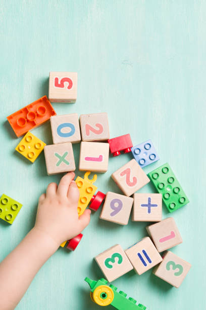 child playing with wooden cubes with numbers and colorful toy bricks on a turquoise wooden background. toddler learning numbers. hand of a child taking toys. - toy stock pictures, royalty-free photos & images