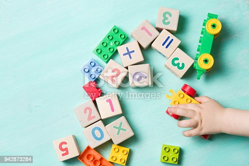 istock Child playing with wooden cubes with numbers and colorful toy bricks on a turquoise wooden background. Toddler learning numbers. Hand of a child taking toys. 942873284