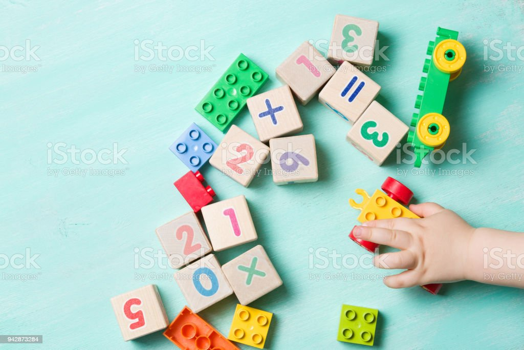 Child playing with wooden cubes with numbers and colorful toy bricks on a turquoise wooden background. Toddler learning numbers. Hand of a child taking toys. stock photo